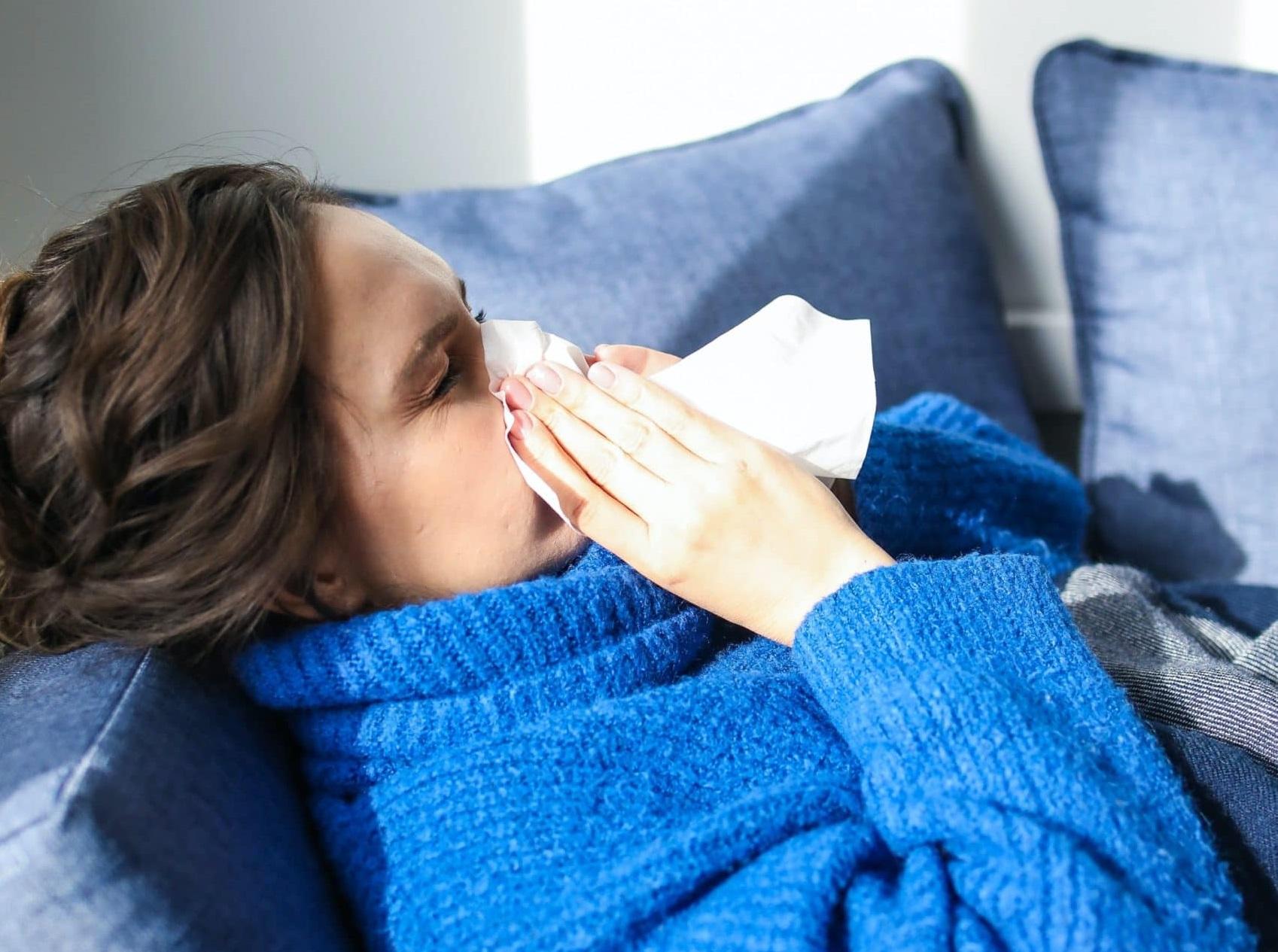Förkyld kvinna i soffa